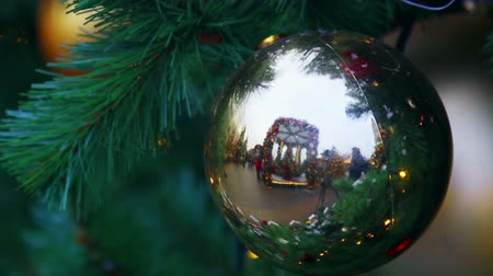 Christmas shiny ball on the Christmas tree at the fair, crowd of people reflected in mirror. Concept christmas and new year holidays. Time lapse Stock Footage