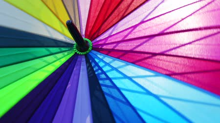 multi-colored umbrella rotates. umbrella made of different color of fabric strips Stock Footage