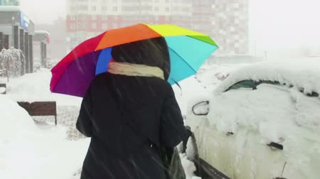 the girl goes under a multi-colored umbrella in heavy snow in the city. slow motion