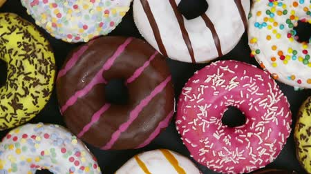 assorted donuts with different fillings and icing on a black background. top view. Rotation video