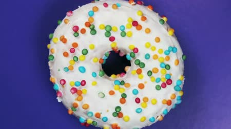 envidraçado : donut with different fillings and icing on blue background. Rotation video