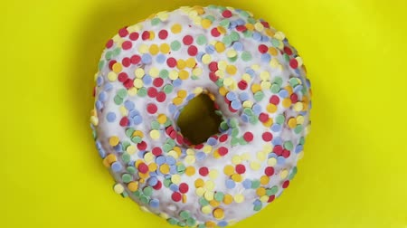 donut with different fillings and icing on yellow background. Rotation video