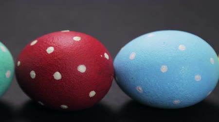 colorful eggs died for the Holy Easter holiday on a black background Stock Footage