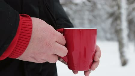 cold : Red Cup with hot drink holding hands in winter forest