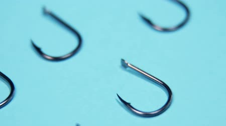 снасти : lots of fishing hooks on blue background. fishing accessories and accessories Стоковые видеозаписи