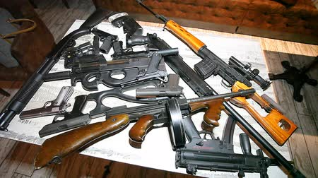 Rifles, pistols and other portable guns are laid out on the table