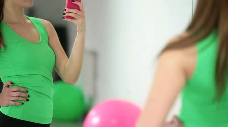 vékony : young woman with smartphone taking mirror selfie in gym