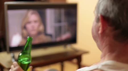 reklama : Man watching tv and drinking beer at home
