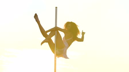 kutup : Sexy attractive girl poledancer performs advanced pole dance tricks at sunset on portable dancing stage over the skyline
