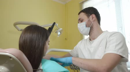 испуг : Male dentist prepares to examine a female patient in the dental clinic, puts on chest sterile cloth.