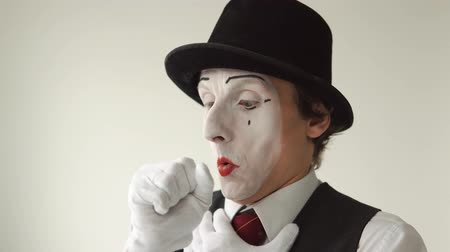 лечит : man mime sick. He has a sore throat, cough, colds. Closeup on white background Стоковые видеозаписи