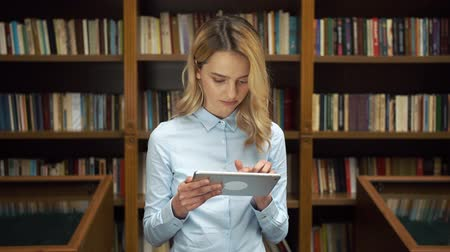 phd : Student works with tablet in the library Stock Footage