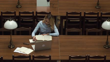 phd : Student works with books and laptop in the library