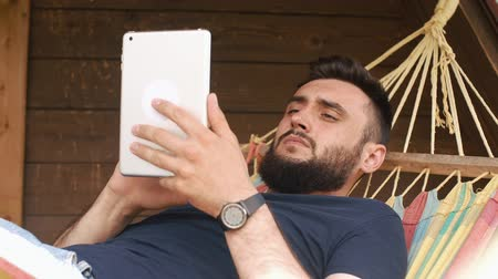 hacienda : A young bearded man uses a tablet, lying in a hammock in a country house Stock Footage