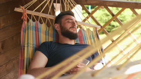 hacienda : A young bearded man sleeping in a hammock in a country house. He sleeps with tablet