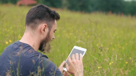 hacienda : a young bearded man uses tablet while sitting on the grass near a country house Stock Footage