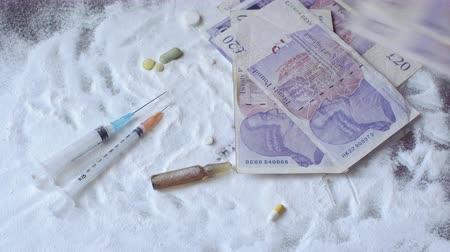 snorting : Dollars fall on the cocaine and pills lying on the table