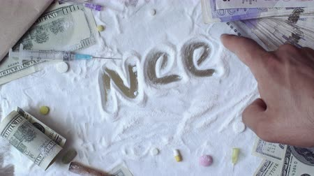 snorting : Man writes need help on the cocaine poured on the table Stock Footage