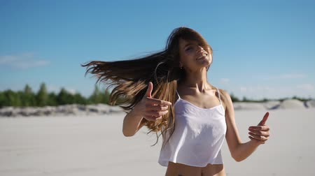 lonely : Woman with long hair has fun dancing on the sand under blue sky