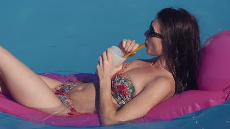 inflável : Beautiful young woman relaxing in swimming pool in summer, lying on inflatable Lounge in sunglases Summer time. She drinks a cocktail