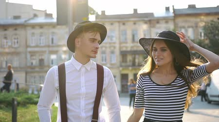 braces : Charming man and woman in black hats walk along the street on the sunset