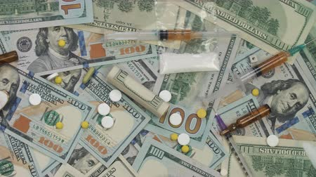 meth : Pills, drugs, cocaine, syringe on dollar bank notes. Paper money rotation. Stock Footage