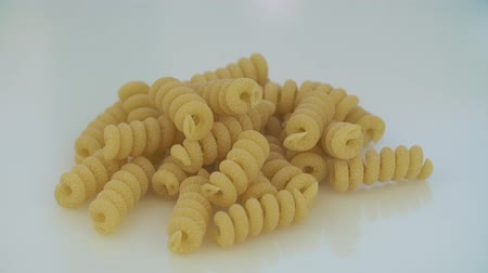 tubular : Closeup of dry maccheroni lying on the table. The frame rotates clockwise.