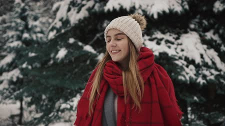 knitted gloves : Young beautiful girl in in warm clothes walking near the Christmas Trees and looking into the camera Slow motion. Portrait of stylish young beautiful girl in a winter park