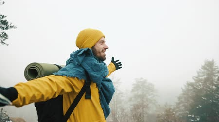 climbed : An excited guy wearing yellow winter clothes has a backpack and a map in his hands. A hitter climbed the mountain and enjoys the view of the trees and a slight fog in winter Stock Footage