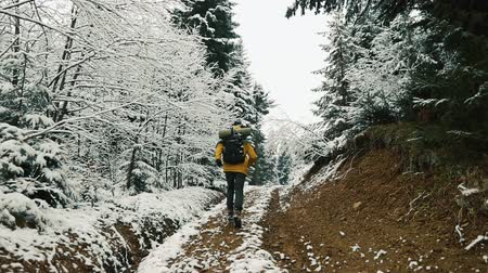 montanhismo : Man in yellow jacket runs up along the path among the mountains covered with snow. Winter time Stock Footage