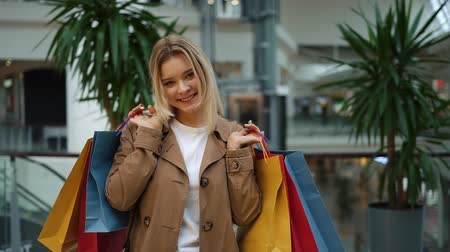портфель : Laughing girl holds shopping bags on her shoulders standing in the mall