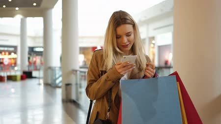 imbibe : Young girl types something in her phone walking around the mall with shopping bags