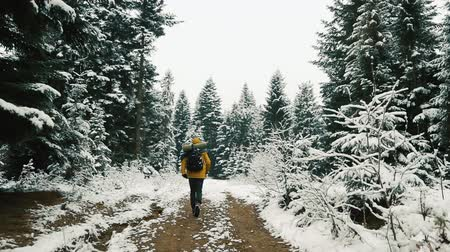 Man in yellow jacket runs up along the path among the mountains covered with snow. Winter time Стоковые видеозаписи
