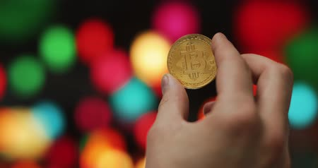 Man hands holding golden crypto currency BTC Bitcoin coins on a blurred colored background