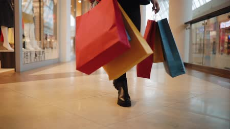 Young blonde woman walks with colorful shopping bags around a shopping mall Стоковые видеозаписи