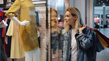imbibe : Charmed young blonde woman walks along a show window with bags in the shopping mall Stock Footage