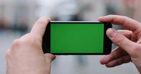 Man holds a smartphone with green screen in his arms standing on the street