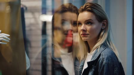 sen : Charmed young blonde woman stands before a show window in the shopping mall