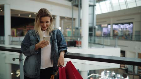 Young woman smiles and types something in her smartphone standing with bags in shopping mall