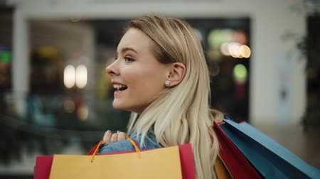 Blonde girl looks over her shoulder walking with shopping bags in the mall