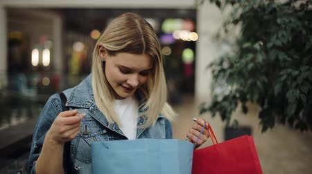 Girl looks inside her shopping bags standing in the shopping mall Стоковые видеозаписи