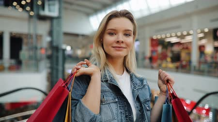 Girl holds shopping bags on her shoulders standing in a mall