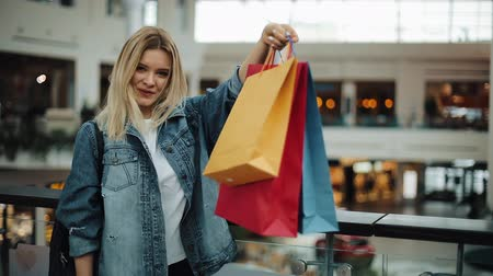 Happy blonde girl looks at her colorful shopping bags standing in shopping mall