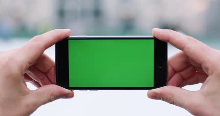 keying : Snow falls over a mans hand holding smartphone with green screen in his arm