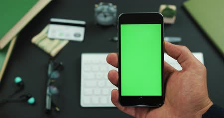 Man holds smartphone with green screen over a working table Vídeos