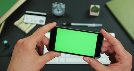 Man holds smartphone with green screen over a working table Stok Video