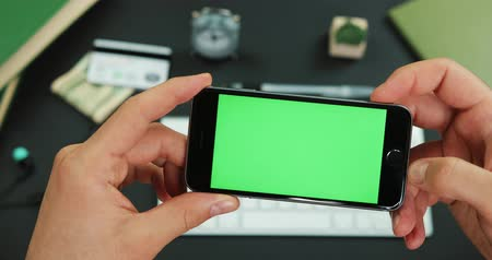 kreditní karty : Man holds smartphone with green screen over a working table and scrolls something on it