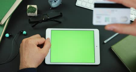 Man holds a tablet with green screen and types information from credit card on a table with green screen