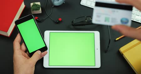 Man holds a smartphone with green screen and types information from credit card on a table with green screen Stock Footage