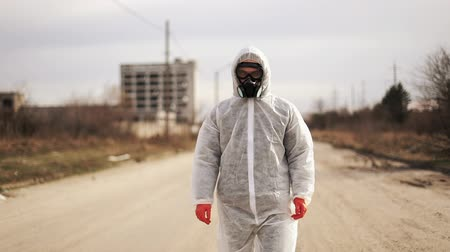 hazmat : Virologist man in protective costume and respirator gas mask walk in a deserted city at the industrial factory background